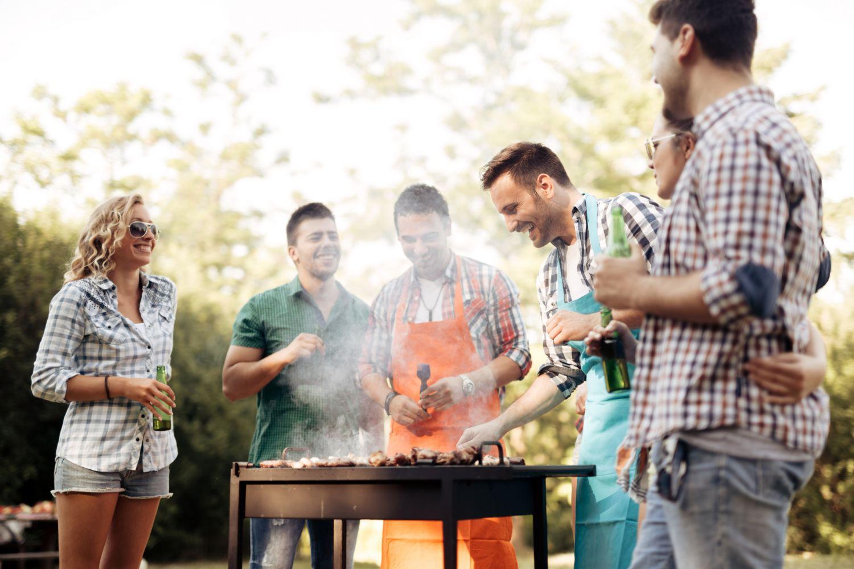 Eine Gruppe Menschen steht um einen Grill versammelt