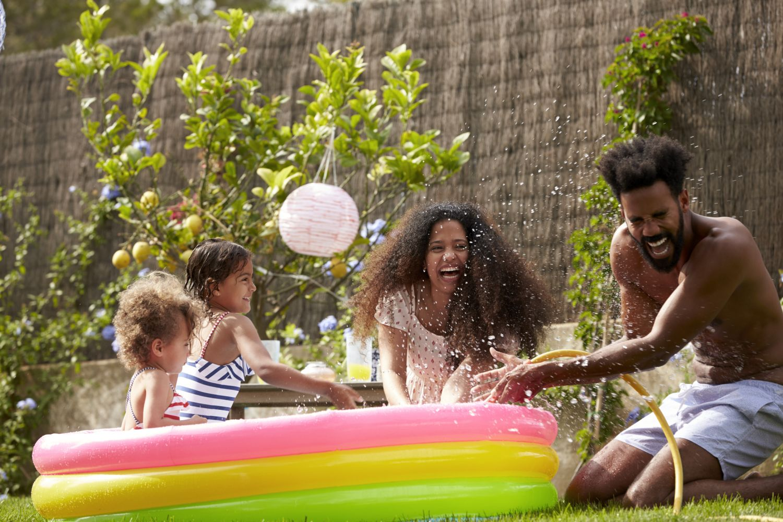 Familie spielt im Pool im Garten